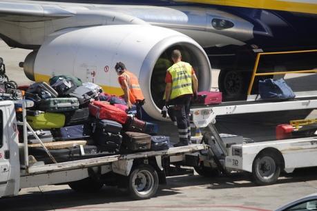 Operarios de rampa de la empresa Swissport descargando equipaje de un avión de Ryanair.